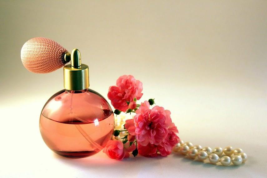 frasco de perfume com flores ao redor